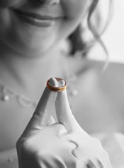 bride holding grooms ring in black and white.